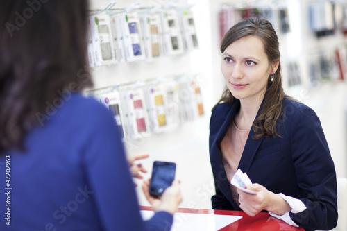 Frau kauft Smartphone mit Bargeld in einem Handy-Shop
