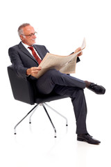 Senior business man reading newspaper