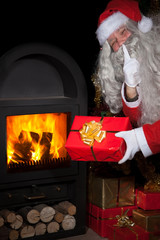 Santa Claus with a gift by the stove