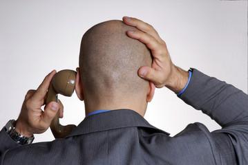 Ejecutivo preocupado al teléfono, de espaldas.