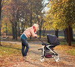 Young mother looking at her child in a stroller