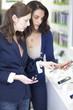 Verkäuferin hilft einem Kunden bei der Wahl eines Smartphone