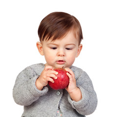 Adorable baby girl looking a red apple