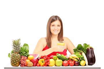 Beautiful young woman with pile of fruit and vegetables
