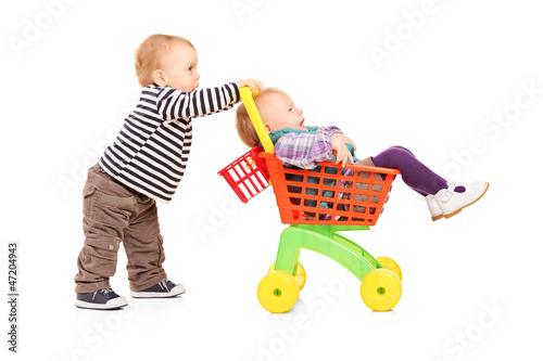 Toddler boy pushing his twin sister in a toy cart