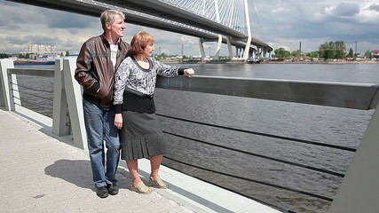 Mature couple admiring the view of the river in summer