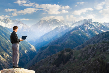 Young businessman using his laptop on the mountain top
