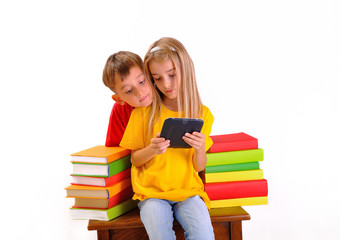 Boy and girl looking at e-book surrounded by several books