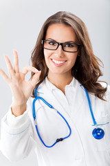 Doctor showing okay gesture, over grey