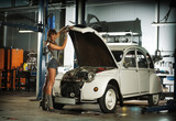 A beautiful brunette woman in a garage fixing an old car