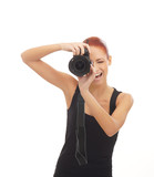 A young happy redhead woman shooting with a camera
