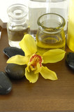 bottle of aromatherapy oil and orchid with stones