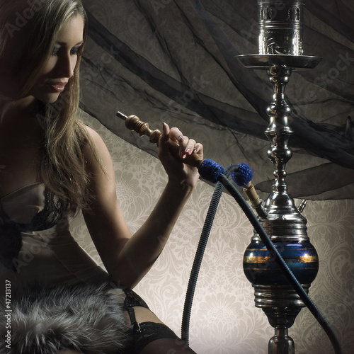 A young blond woman smoking a hookah on a silk background