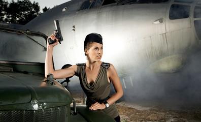 A woman in military clothes holding a gun near an airplane