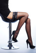 Sexy legs of a woman in black erotic lingerie sitting on a chair