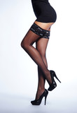 Sexy legs of a slim woman in black erotic stockings