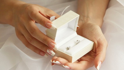 Bride holding a box with earrings in her hands