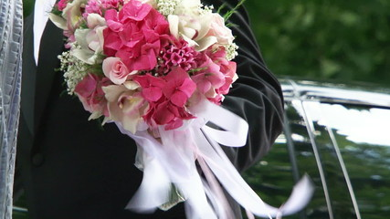 Bride and groom holding wedding bouquet by turn.
