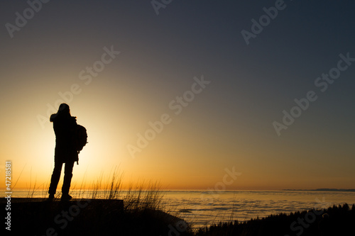 silhouette of woman standing in sunset