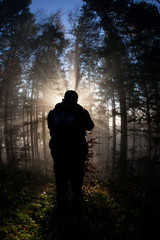 silhouette of man standing in sunbeams in forest