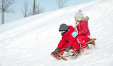 Fototapety Two little kids - boy and girl - sliding with sledge in the snow