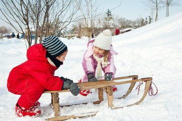 Two little kids having fun with sled in the snow.
