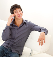 Happy smiling young man sitting on the leather sofa and talking