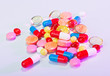 Pills, tablets and drugs heap, medical concept in violet colors