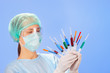 Young woman doctor with many multicolor syringes in hands on blu