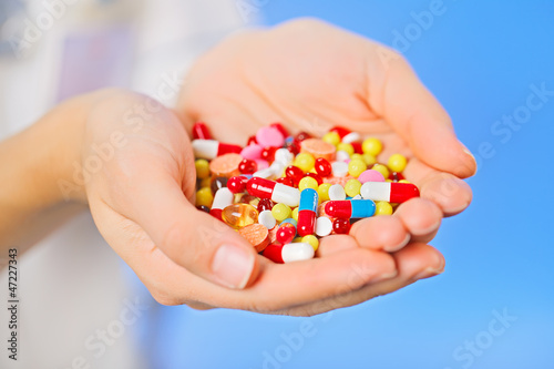 Pills, tablets and drugs heap in doctor's hand on blue backgroun
