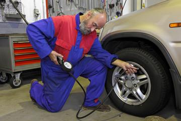 garagiste vérifiant la pression des pneus