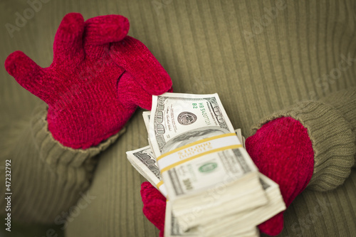 Woman Wearing Mittens Holding Stacks of Money with Red Ribbon