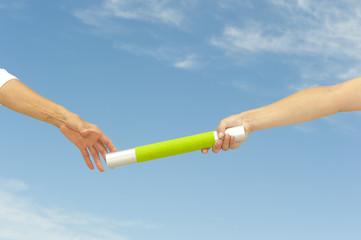 Hands reaching baton for teamwork