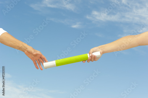 Hands reaching baton for teamwork