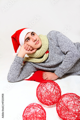 Young man with a scarf, hat santa claus and red balls isolated o