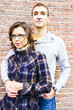 Portrait of love couple embracing looking happy against wall bac