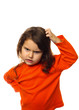 Brunette kid in orange sweater, scratching his head thinking, is