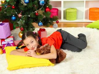 Little girl sleeping near christmas tree