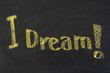 hand writing 'I dream' in the blackboard with chalk
