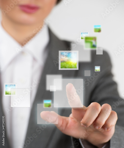 Young business woman pushing a button on a virtual touch screen