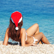Young woman in santa hat sitting on the beach