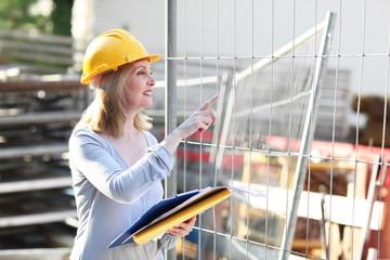 Bauleiterin zeigt auf Baustelle