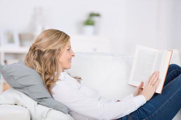 frau liest ein buch auf dem sofa