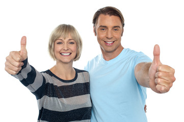 Confident couple showing thumbs up sign