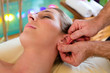 Woman enjoying head massage in a spa