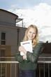 Junge Frau am Balkon klammert ihren Mietvertrag an sich