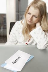 Junge Frau in ihrer Wohnung blickt niedergeschlagen auf Rechnung