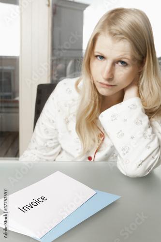 Junge Frau in ihrer Wohnung mit Rechnung am Tisch