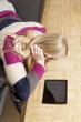 Frau liegt gemütlich auf der Couch und blickt auf Tablet PC