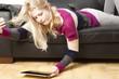 Frau liegt auf Couch und benutzt ihr Tablet PC